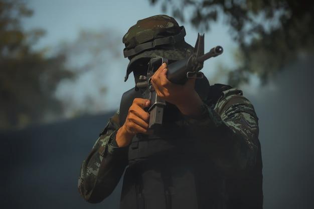 Soldat in schutzuniform mit gewehr. spezialeinheiten soldat sturmgewehr mit schalldämpfer.