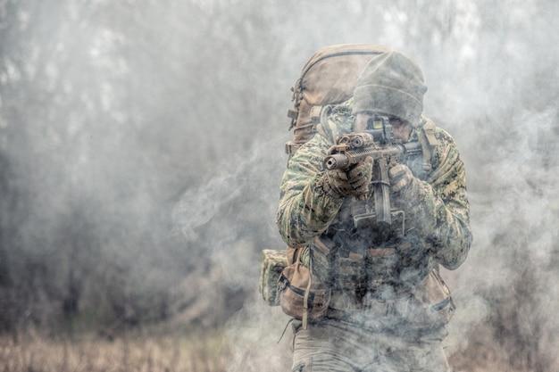 Soldat in tarnuniform, militärmunition tragend, dienstgewehre zielen, sich gegenseitig bedecken, auf konkurrenten schießen, feinde durch nebelwand angreifen
