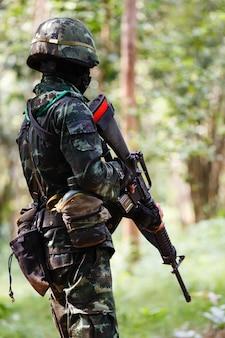 Soldat in uniform mit waffe Premium Fotos