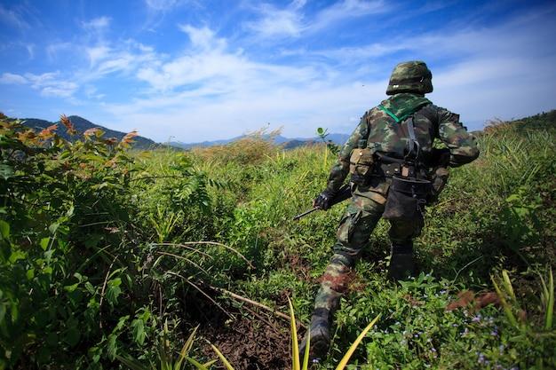 Soldat läuft im feld unter blauem himmel