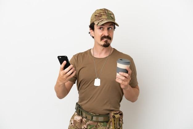 Soldat mann isoliert auf weißem hintergrund hält kaffee zum mitnehmen und ein handy, während er etwas denkt