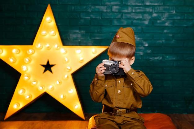 Soldat mit filmkamera. fotograf mit kamera in den händen. kinderkriegskorrespondent während des zweiten weltkriegs. junge in russischer militäruniform mit kamera. militärischer wiederaufbau.