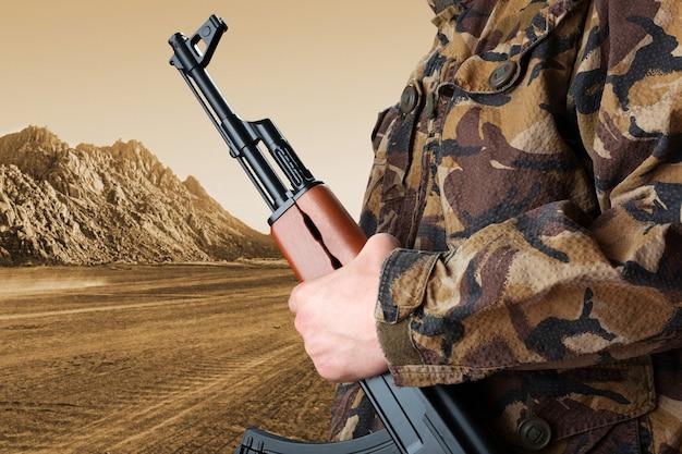 Soldat mit gewehr ak-47 gegen wüste