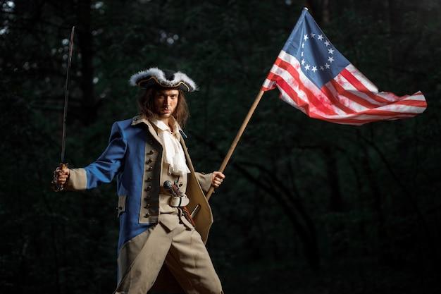 Soldat patriot rebell während des unabhängigkeitskrieges der vereinigten staaten mit flagge, die sich darauf vorbereitet, mit säbel anzugreifen