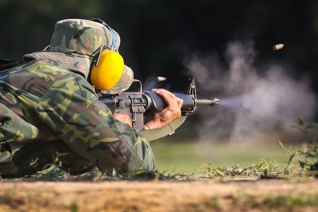 Soldat schießt gewehrgewehr, um mit kugelpatrone in der luft zu zielen