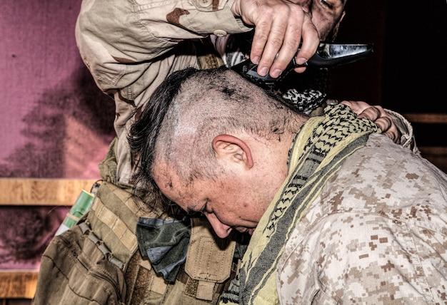 Soldat schneidet kameraden die haare mit trimmer. us-marine rasieren freunde den kopf mit clipper unter kampfbedingungen. anwerber, der sich auf den dienst in streitkräften vorbereitet, indem er einen ersten haarschnitt erhält