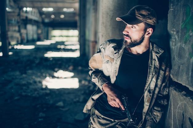 Soldat steht und lehnt sich an betonmauer. er schaut nach links. guy hält eine schwarze waffe in der rechten hand. außerdem trägt er spezielle bezüge zum körperschutz.