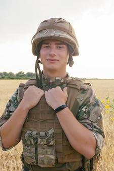 Soldatenmann, der gegen ein feld steht. porträt eines glücklichen militärsoldaten im bootcamp. soldat der us-armee in der mission. krieg und emotionales konzept.