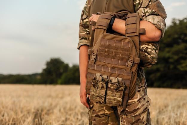 Soldatenmann, der gegen ein feld steht. soldat im militäroutfit mit kugelsicherer weste. foto eines soldaten in militärausstattung, der eine waffe und eine kugelsichere weste auf orangefarbenem wüstenhintergrund hält.