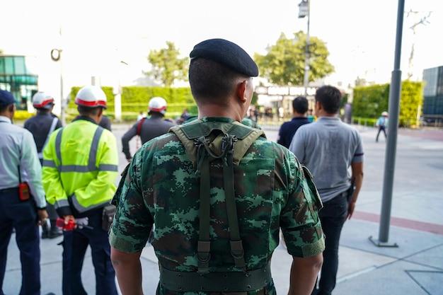Soldatenrücken mit männlichen polizisten und wachen im hintergrund, stand in der reihe und wartete auf den kommandanten.