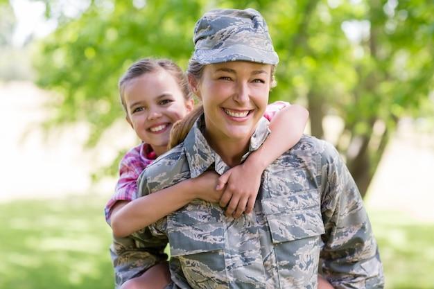Soldatin, die ihrer tochter im park eine huckepackfahrt gibt
