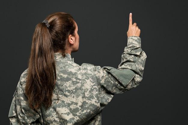 Soldatin drückt zeigefinger auf einen unsichtbaren bildschirm