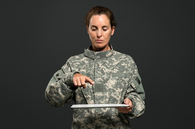Soldatin drückt zeigefinger auf tablette