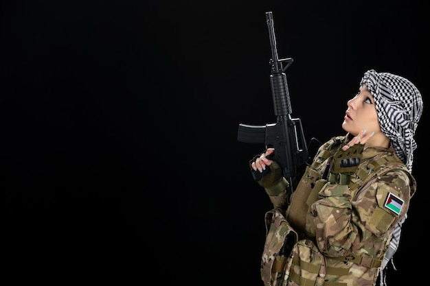 Soldatin in militäruniform mit gewehr an der schwarzen wand