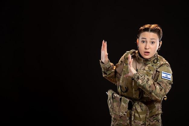 Soldatin in tarnung an der schwarzen wand
