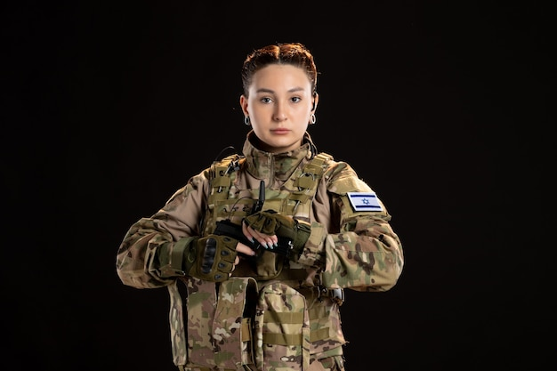 Soldatin in tarnung mit dem ziel einer waffe auf die schwarze wand