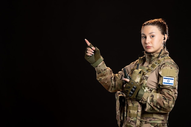 Soldatin in tarnung mit granate an der schwarzen wand