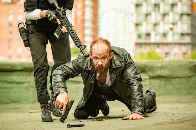 Soldatin, mörderin eines spionageagenten oder polizistin mit einer waffe in der hand, die mit vorgehaltener waffe einen auf dem boden liegenden mann hält
