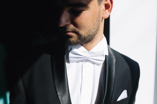 Solider brünetter bräutigam im innenlicht des schwarzen anzugs