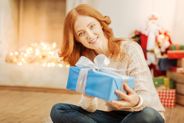 Soll ich es jetzt öffnen? schöne frau, die auf dem boden mit ihren gekreuzten beinen mit einem fröhlichen lächeln auf ihrem gesicht sitzt, während sie ein schön verpacktes weihnachtsgeschenk hält.