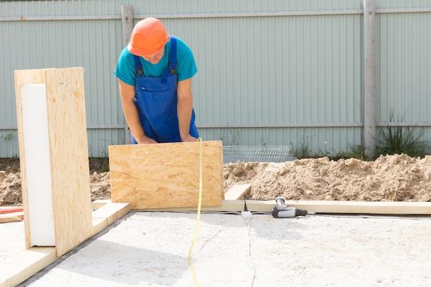 Solo beschäftigter männlicher bauarbeiter mit orangefarbenem helm, der immobilien hauswand baut.