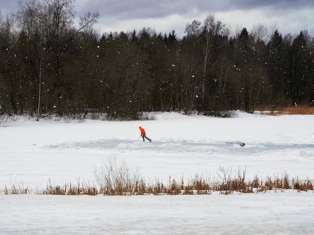 Solo-training eines hockeyspielers auf einer behelfsmäßigen eisbahn auf einem zugefrorenen see. gesunder lebensstil, sportkonzept.