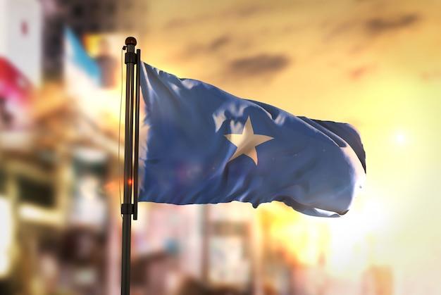 Somalia-flagge gegen stadt verschwommen hintergrund bei sonnenaufgang hintergrundbeleuchtung