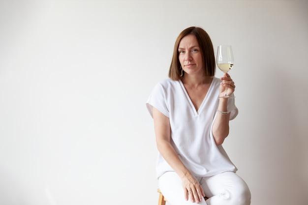 Sommelier des kaukasischen brünetten mädchens, das glas weißwein hält