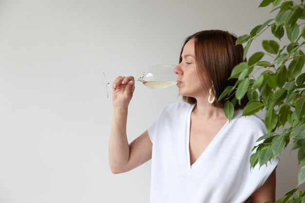 Sommelier des kaukasischen brünetten mädchens, das weißwein vom glas trinkt