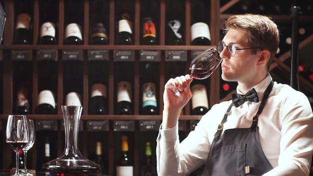 Sommelier hält ein glas wein in der hand, schaut auf das glas wein und schmeckt das aroma von wein im glas
