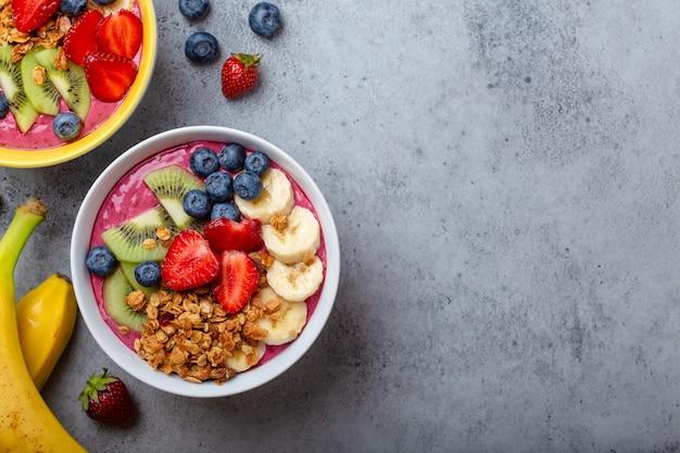 Sommer-acai-smoothie-schalen mit erdbeeren, banane, blaubeeren, kiwi und müsli auf grauem betonhintergrund. frühstücksschüssel mit obst und müsli, nahaufnahme, draufsicht, platz für text