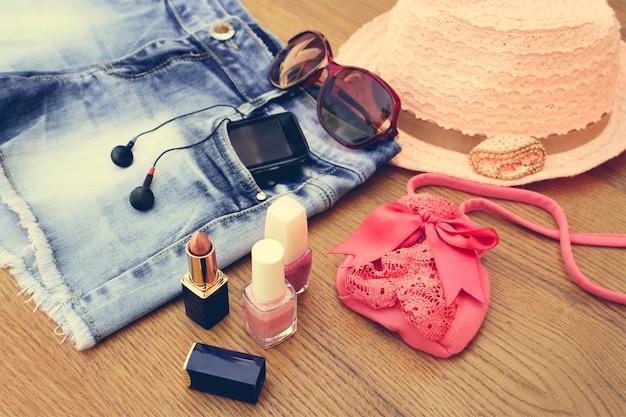 Sommer accessoires für frauen: sonnenbrille, perlen, jeansshorts, handy, kopfhörer, sonnenhut, handtasche, lippenstift, nagellack. getöntes bild