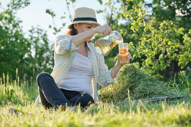 Sommer-außenporträt der frau mit natürlichem getränk aus erdbeer-minz-kräutern, frauengartenarbeit, gesunder lebensstil und essen, goldene stunde
