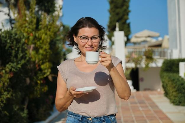 Sommer-außenporträt der reifen lächelnden frau, die mit tasse kaffee geht