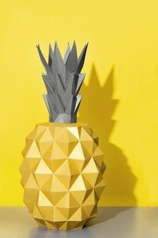 Sommer design hintergrund mit form der ananas aus papier mit hartem licht. trendfarbe von 2021, illiminierendes gelb und ultimatives grau.