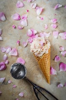 Sommer erfrischende desserts. vegane diätkost. eiscreme mit den rosafarbenen blumenblättern und den scheiben der mandel, in den klassischen waffeleiscremekegeln, auf einer beige hellen konkreten tabelle. copyspace draufsicht