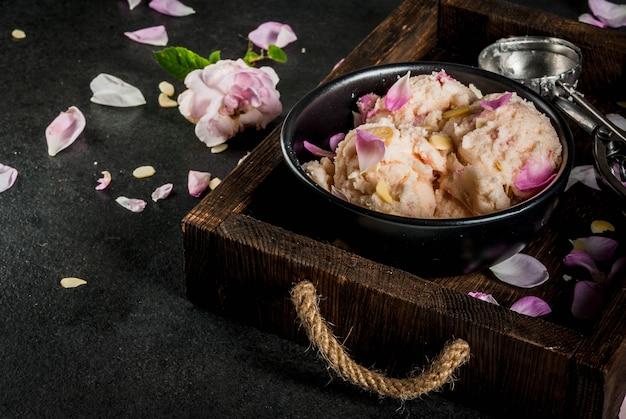 Sommer erfrischende desserts. vegane diätkost. eiscreme mit den rosafarbenen blumenblättern und scheiben von mandeln, auf hölzernem altem behälter, auf schwarzer steintabelle. mit löffel für eis und zutaten.