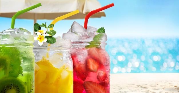 Sommer erfrischende exotische getränkecocktails in gläsern mit strohhalmen auf seelandschaft mit bokeh-sonnenlichthintergrund.