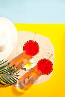 Sommer erfrischender cocktail am strand. sand, muscheln und plumeria frangipani.