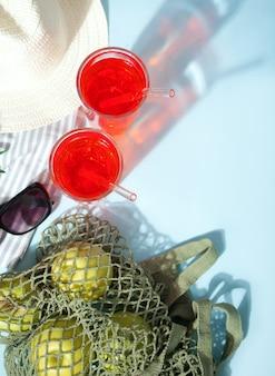Sommer erfrischender getränkecocktail bei einem picknick mit grünen äpfeln in einer netztasche, sonnenbrille und hut.
