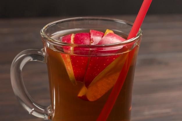 Sommer erfrischendes getränk mit geschnittenen äpfeln. teil des rahmens. dunkler holzhintergrund. nahaufnahme.