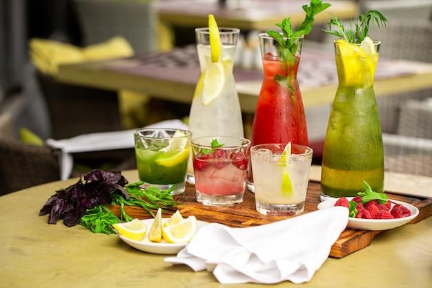 Sommer-erfrischungsgetränke, eine reihe von limonaden. limonaden in krügen auf dem tisch, deren zutaten sie hergestellt haben, sind herum angeordnet.