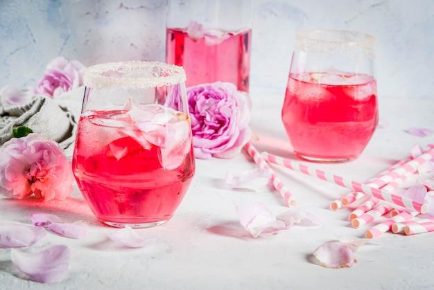 Sommer-erfrischungsgetränke hellrosa rosencocktail mit rosetee rosenblättern zitrone auf einem weißen steinbetontisch mit gestreiften rosa röhrenblättern und rosenblüten