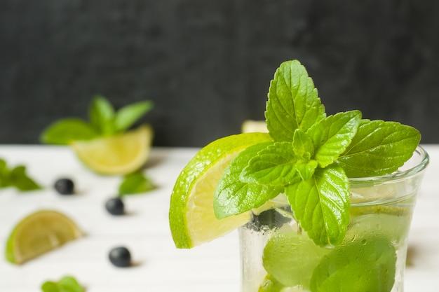 Sommer erfrischungsgetränke limonade oder cocktail mojito mit limone frische minze heidelbeereis.