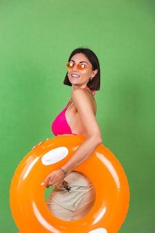 Sommer fit sportliche frau in rosa bikini und leuchtend orangefarbenem aufblasbarem ring und sonnenbrille auf grün, fröhlich fröhlich aufgeregt fröhlich positiv