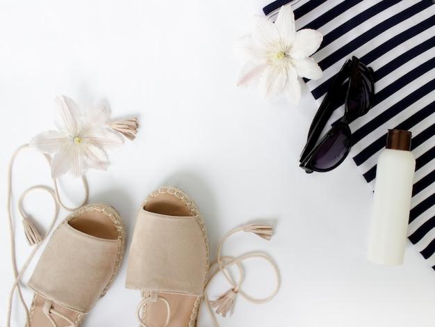 Sommer flach legen sommersandalen weiße blumen sonnenbrille und ein kreativer hintergrund mit weißer flaschenoberseite