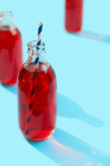 Sommer gefrorener cranberry-punch-cocktail in der flasche auf blauem hintergrund
