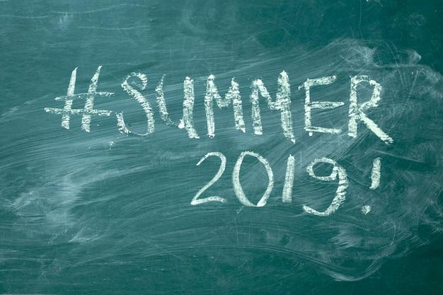 Sommer-hashtag handschriftlich mit weißer kreide auf einer grünen tafel.