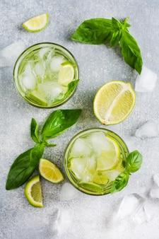 Sommer hausgemachte limonade aus limette, zitrone, gurke und basilikum mit eis in glas auf einem alten beton.