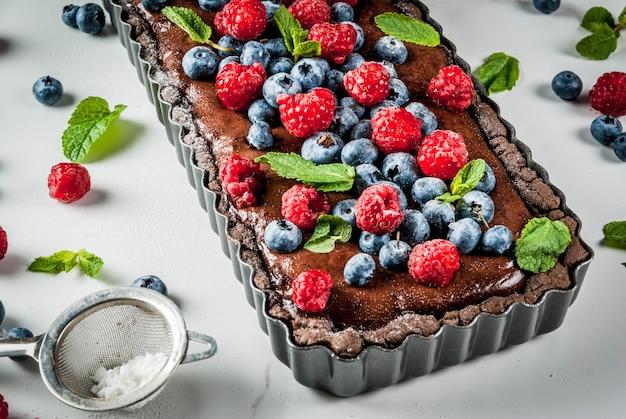 Sommer hausgemachtes gebäck. schokoladenkuchentarte mit schokoladencreme, frische rohe beeren heidelbeer himbeere, dekoriert mit minze, puderzucker. auf weißer marmortabelle copyspace